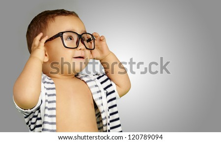 Portrait Of Baby Boy Wearing Eyeglasses against a grey background