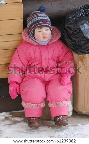 Portrait of baby by the trash bag in winter time