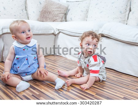 Portrait of baby girl and baby boy playing at home on the floor.