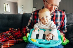 Portrait of baby girl and her grandpa playing with piano toy. Little child sitting on mans lap in living room. Childcare and infancy concept