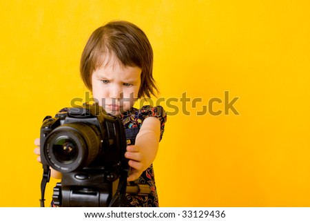 Portrait of baby girl holding photo camera isolated on yellow background