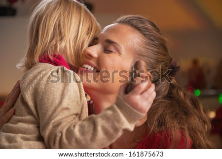 Portrait of baby hugging mother in christmas decorated kitchen