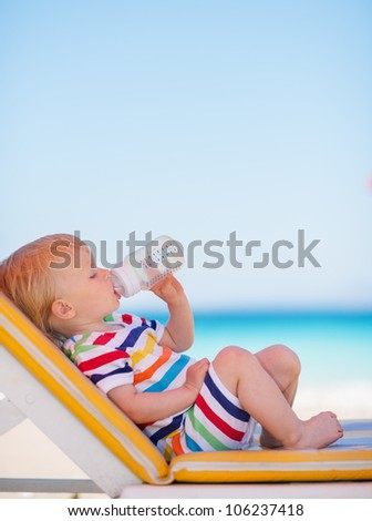 Portrait of baby on sun bed drinking water - stock photo