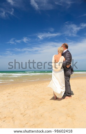 Portrait of back - couple standing together on coast of beach
