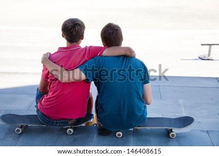 Portrait of back two friends skateboarders on the street