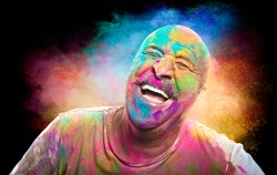Portrait of bald cheerful man with colored face celebrating holi color festival. Man having fun with colorful powder.