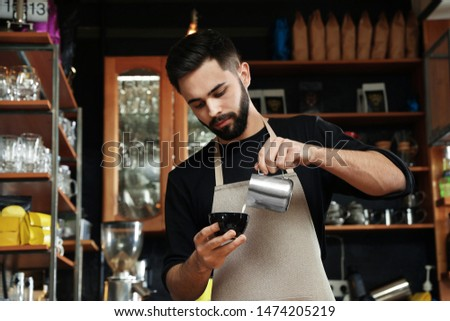 Portrait of barista pouring milk into cup of coffee against bar shelves in cafe