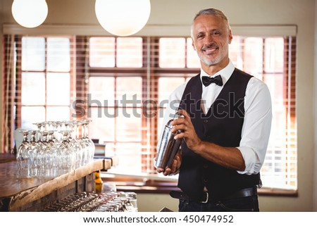Portrait of bartender mixing a cocktail drink in cocktail shaker at bar counter #450474952