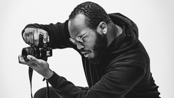 Portrait of beard African American professional cameraman with glasses in the studio.