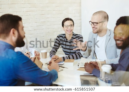 Portrait of bearded Afro-American employee looking at camera with toothy smile while having project discussion with his colleagues in meeting room, view through glass wall #615851507