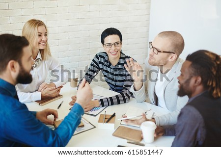 Portrait of bearded businessman in eyeglasses expressing his point of view on topical issue while sitting in meeting room with multiethnic group of coworkers #615851447