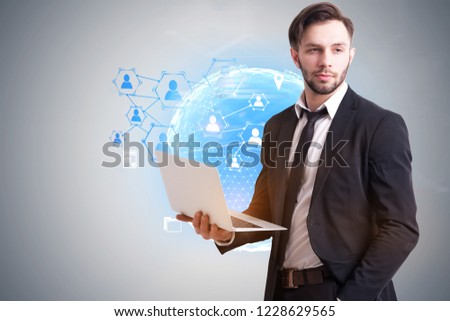 Portrait of bearded businessman wearing suit and black tie and holding laptop standing near concrete wall with earth hologram and people network icons. Toned image