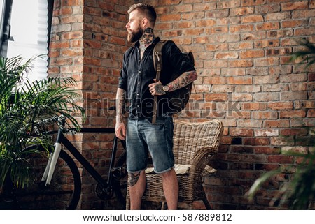 Portrait of bearded casual hipster male with tattoos on his arms holds urban backpack in a room with single speed bicycle.