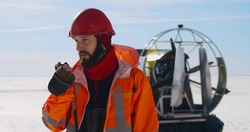 Portrait of bearded coast guard member talking on portable radio standing on frozen lake in winter with air-boat on background. Life rescuer in uniform reporting on walkie-talkie