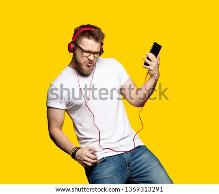 Portrait of bearded guy enjoying metal song and imagining playing bass guitar. Model posing and dancing in studio. Male wearing red headphones and casual clothes #1369313291