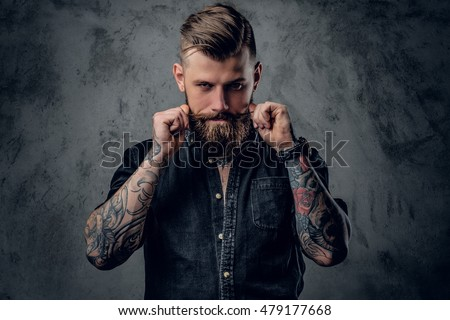 Portrait of bearded hipster with tattooe on his arms.