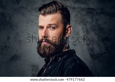 Portrait of bearded male in black shirt with tattoo on his neck.