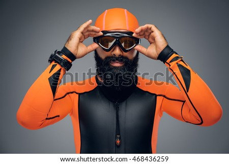 Portrait of bearded male in scuba diving mask and orange neopren diving suit isolated on grey background. #468436259