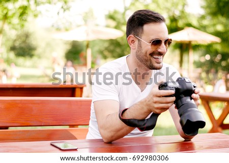 Portrait of bearded man holding dslr while sitting in cafe. #692980306