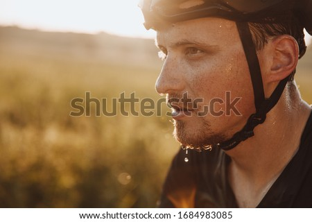 Portrait of bearded man in black helmet feeling tired because of riding bike outdoors. Strong cyclist with drops of sweat on his face  having break during training. Photo stock ©