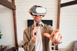Portrait of bearded man wearing virtual reality glasses watching video of rock concert and enjoying musical performance. Man with hipster beard singing along to favorite song. Music concept