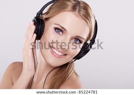 Portrait of beautiful adult smiling blonde girl listen to the music with headphones