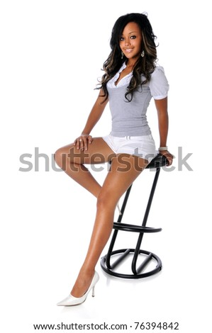 Portrait of beautiful African American woman sitting on stool isolated over white background - stock photo