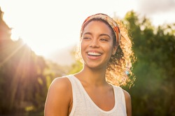 Portrait of beautiful african american woman smiling and looking away at park during sunset. Outdoor portrait of a smiling black girl. Happy cheerful girl laughing at park with colored hair band.