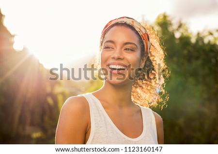 Photo of Portrait of beautiful african american woman smiling and looking away at park during sunset. Outdoor portrait of a smiling black girl. Happy cheerful girl laughing at park with colored hair band.