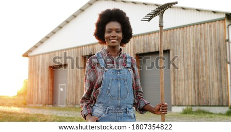 Portrait of beautiful African American young woman with pitchfork farmer standing in field at shed on background and smiling to camera. Pretty female with smile and fork at farm. Countryside concept.