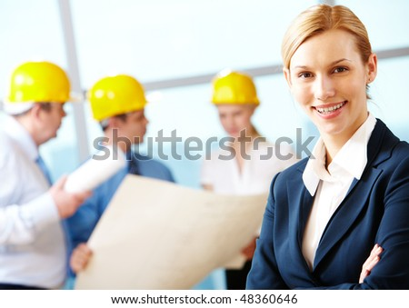 Portrait of beautiful architect folding arms on the background of workers