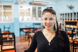 Portrait of beautiful Asian female teacher wearing face shield smiling while standing  in classroom. New normal lifestyle during corona virus or Covid-19 crisis