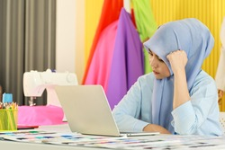 Portrait of beautiful asian muslim woman designer with hijab holding and using computer laptop in her home working studio room with colorful cloth and electronic sewing machine work form home concept.