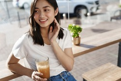 Portrait of beautiful asian woman drinking ice latte in cafe by the window, looking aside and smiling tenderly.
