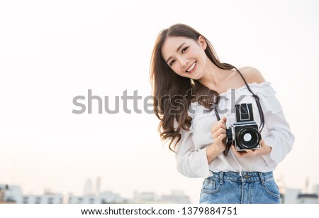 Portrait of beautiful asian woman photographer fashion look taking photo. Pretty cool young woman model with retro film camera curly hair outdoors over rooftop sky with copy space