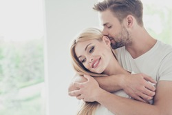 Portrait of beautiful attractive sweet lovely charming cute nice adorable couple, spouses, husband and wife in white t-shirts on honey-moon at hotel, embracing in light interior room