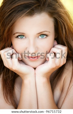 Portrait of beautiful attractive young woman propping up her face with hands at summer green park