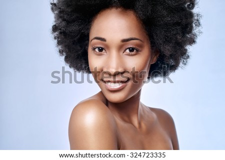 Portrait of beautiful black african model smiling in studio with smooth complexion flawless skin, skincare beauty concept