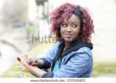 Portrait of beautiful black woman in urban background with red hair
