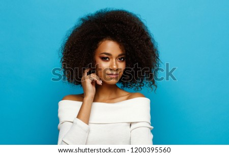 Portrait of beautiful black woman with an afro hairstyle isolated on blue background