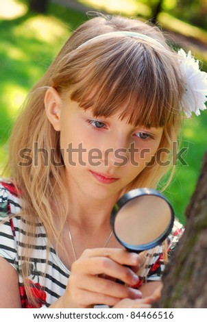 portrait of beautiful blond girl looking through magnifying glass  in the park