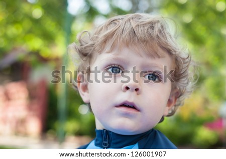 Portrait of beautiful blond toddler boy in green summer garden