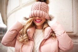 Portrait of beautiful blond woman dressed in pink warm clothes, padded jacket, white sweater, pants and knitted hat with fur pumpon walking in the street of the city. Urban style concept