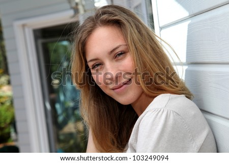 Portrait of beautiful blond woman leaning against home wall