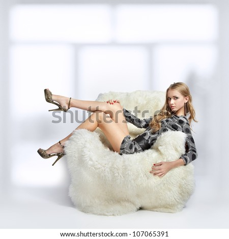 portrait of beautiful blonde blue-eyed girl sitting in big furry arm-chair