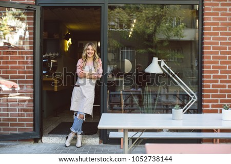 Portrait of beautiful blonde Caucasian woman waitress wearing apron and standing in front of her coffee shop.