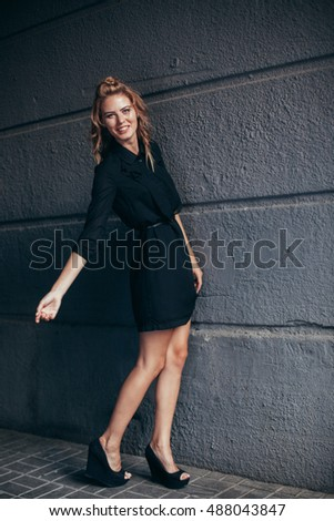 Portrait of beautiful blonde Caucasian young woman in a classic black dress elegant clothes standing near the dark wall in the transition. sexy. ideal professional hair and makeup. laughing #488043847