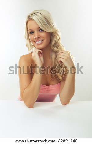 Portrait of beautiful blonde girl at table smiling