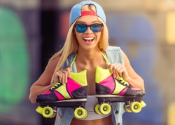 Portrait of beautiful blonde girl in cap and glasses looking at camera and smiling while standing with her rollers in skate park