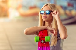 Portrait of beautiful blonde girl in glasses looking away while leaning on her skateboard